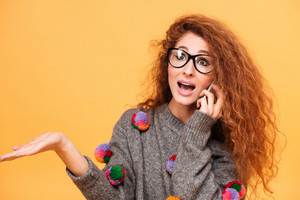 Amazed redhead woman with long hair and eyeglasses talking on mobile phone isolated over orange background