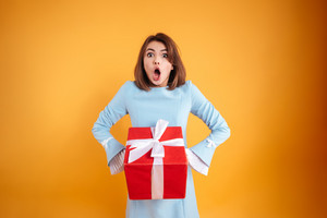 Amazed shocked young woman with opened mouth holding present box over yellow background