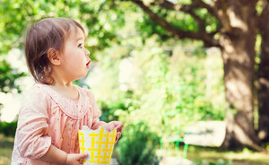 Amazed toddler girl playing outside at a bright sunny day