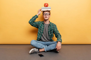 Amazed young man with book and apple on his head sitting with legs crossed over yellow background