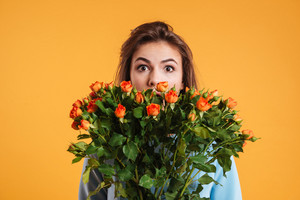 Amazed young woman hiding her face behind bouquet of roses over yellow background