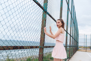 Amazed young woman in pink top and skirt standing near chain link fence