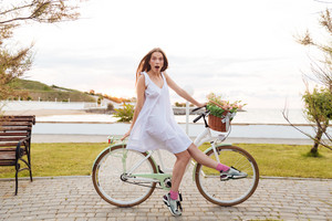 Amazed young woman riding bicycle and having fun in summer park