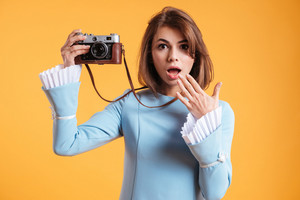 Amazed young woman taking pictures with old vintage camera over yellow background
