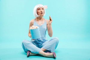 Amazed young woman with marshmallows and magic stick sitting with legs crossed