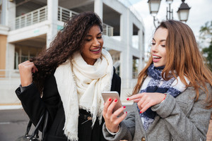 Amazing two young ladies looking on a smartphone and pointing at screen surprised. Caucasian girl wearing scarf in a cage print. African lady wearing burgundy scarf.