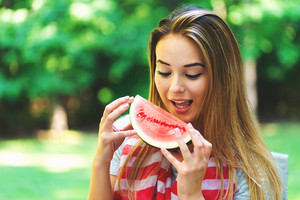 American girl with red striped scarf eating watermelon outside