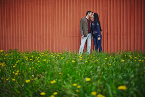 Amorous couple in casualwear kissing on green lawn