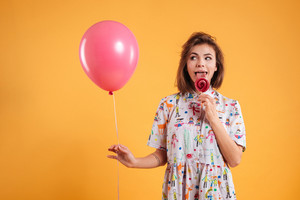 Amusing joyful young woman with pink balloon eating lollipop over yellow background