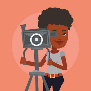 An african-american cameraman looking through movie camera on a tripod. Young cameraman with professional video camera. Female cameraman taking a video. Vector flat design illustration. Square layout.
