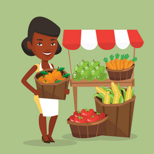 An african greengrocer standing near stall with fruits and vegetables. Greengrocer standing near market stall. Greengrocer holding basket with fruits. Vector flat design illustration. Square layout.