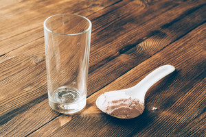 An empty glass and a spoon of protein powder on wooden table