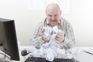 Angry and overworked office worker with a heap of paper at the office desk. To much work.