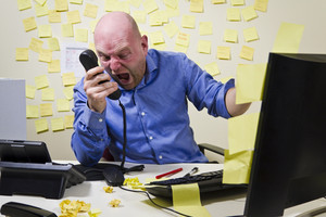 Angry boss / man screaming on the phone at his office.