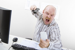 Angry Businessman Aiming Gun On Mobile Phone At Desk