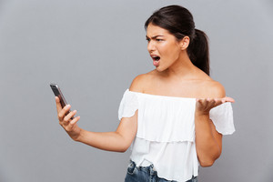 Angry casual brunette woman using smartphone isolated on a gray background