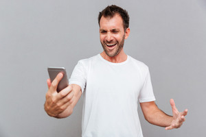 Angry casual man holding smartphone isolated on a gray background