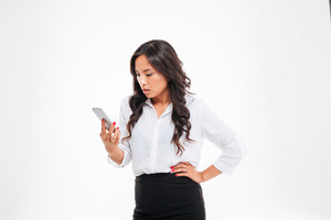 Angry confused asian businesswoman looking at smartphone isolated on a white background