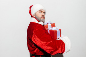 Angry frowning man santa claus holding gift boxes