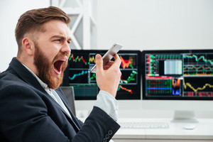 Angry irritated bearded young businessman screaming in smartphone in office