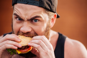 Angry irritated young man in cap eating hamburger outdoors
