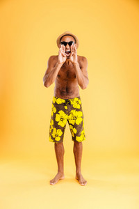 Angry mad african man in swimwear standing and shouting isolated on a orange background