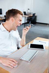 Angry mad young businessman talking on mobile phone and shouting in office