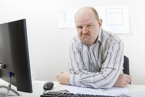 Angry Mature Businessman Sitting At Desk