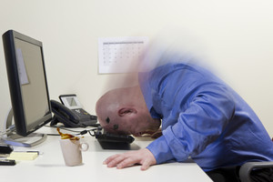Angry office worker / businessman beats his head hard into the PC keyboard. Copy Space.