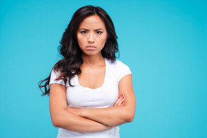 Angry pretty asian woman standing with arms crossed isolated on the blue background