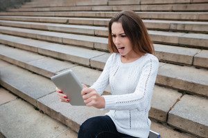 Angry pretty young woman sitting on stairs and using tablet