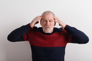 Angry senior man in red and blue sweater holding head. Studio shot against white wall.