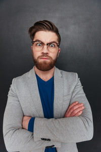 Angry serious young businessman in glasses standing with arms crossed