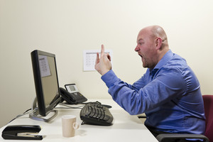 Angry worker give finger to his computer.