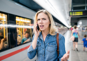 Angry young blond woman in denim shirt with smartphone making phone call. Standing at the underground platform, waiting to enter a train.