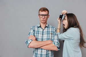 Annoyed hipster man in eyeglasses standing with arms folded while being photographed by a woman isolated on the gray background