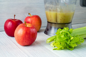 Apples and a bunch of celery, and a food processor with a smoothie on a white table. Concept of healthy eating.