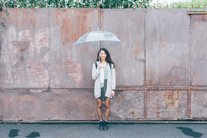 Asian beautiful young woman outdoor in the city holding umbrella in a rainy day - happiness, carefree, freedom concept