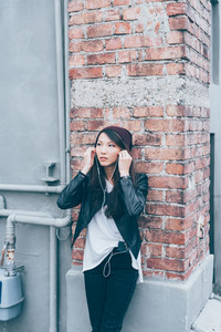 Asian beautiful young woman outdoor in the city listening music with earphones and smart phone - relaxing, music, enjoying concept