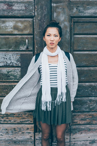 Asian beautiful young woman outdoor in the city posing leaning on a wooden wall looking camera serious - indipendent, girl power, confidence concept