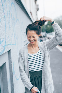 asian beautiful young woman playing with her hair laughing - confident, customer, girl power concept