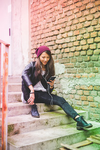 Asian beautiful young woman sitting outdoor listening music with earphones and smartphone hand hold - music, technology, leisure concept
