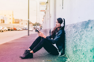 Asian beautiful young woman sitting outdoor listening music with headphones and smartphone hand hold - music, technology, leisure concept