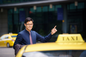 Asian business man standing near office buildings, calling yellow taxi and entering in car