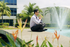 Asian businessman relaxing outside office building. The man does yoga on a bridge and smiles with eyes closed in prayer position
