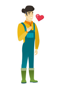 Asian farmer in coveralls holding hand on his chest. Full length of young happy farmer with hand on his chest and heart flying nearby. Vector flat design illustration isolated on white background.