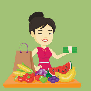 Asian female shopper standing at the table with grocery purchases. Young shopper holding money in hand in front of table with grocery purchases. Vector flat design illustration. Square layout.