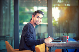 asian freelance man working on computer laptop toothy smiling face
