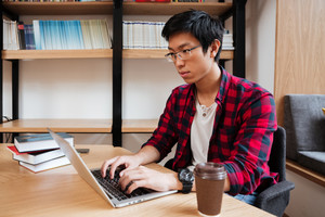 Asian male dressed in shirt in a cage and wearing glasses using laptop at the library while drinking coffee. Looking at laptop.