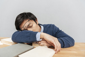 Asian man asleep on the table. gray background